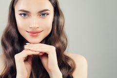 Pretty female face closeup portrait. Clear skin, manicured nails, curly hair and cute smile stock image