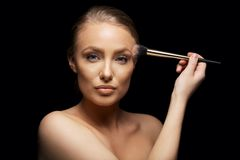 Pretty female fashion model putting on make up Royalty Free Stock Photos
