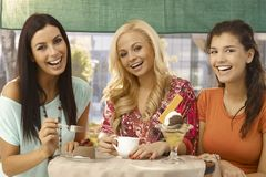 Pretty female friends by cafe table smiling Royalty Free Stock Photos