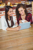 Pretty female friends enjoying a coffee using tablet pc Royalty Free Stock Photo