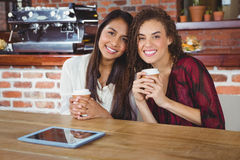Pretty female friends enjoying a coffee using tablet pc Stock Photography