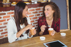 Pretty female friends enjoying a coffee using tablet pc Royalty Free Stock Photos