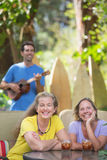 Pretty Female Friends Outdoors. Two smiling female friends near ukulele player in Hawaii Royalty Free Stock Photography