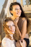 Pretty Female Friends Sitting on Wooden Stairs Royalty Free Stock Photography