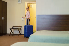 Pretty female guest at threshold of hotel room Stock Image
