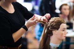 Pretty female hairdresser/haidressing apprentice/student. Training on an apprentice head stock photography