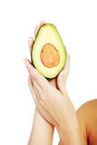 Pretty female hands holding fresh avocado Stock Photography