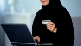 Pretty female in hijab entering credit card number on laptop, shopping online stock images