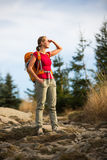 Pretty, female hiker going downhill Stock Photos