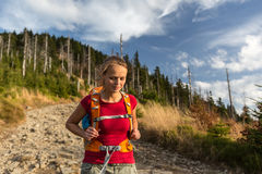 Pretty, female hiker going downhill Royalty Free Stock Images