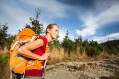 Pretty, female hiker going downhill Royalty Free Stock Photography
