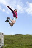 Pretty female hiker jumps from a tree stump Royalty Free Stock Photos