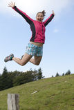 Pretty female hiker jumps from a tree stump Royalty Free Stock Images