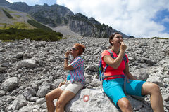 Pretty female hikers eating muesli bar in mountains, enjoying granola cereal bars, living healthy active lifestyle in mountain nat royalty free stock image