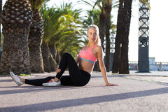 Pretty female jogger with slender figure taking break after workout outdoors. Portrait of a young fit woman dressed in sportswear sitting on the road and resting stock image