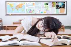 Pretty female learner sleeping on the books. Female high school student sleeping in the classroom above the books on the table Stock Images