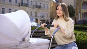 Pretty female looking at baby in carriage sitting on bench, motherhood happiness. Stock footage stock footage