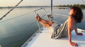 Pretty female lying on deck of sailing yacht, enjoying rest. Stock footage stock video