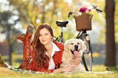 Pretty female lying down with dog in park Royalty Free Stock Photography