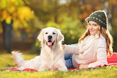 Pretty female lying down with a dog in a park Stock Images