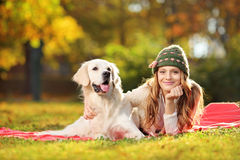Pretty female lying down with her dog in a park Royalty Free Stock Photography
