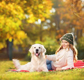 Pretty female lying down with her labrador retriever dog in a pa Royalty Free Stock Photos