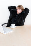 A pretty female manager leaning back in a chair. With strong eye contact Stock Photos