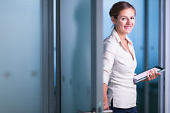 Pretty female manager/office clerk/lawyer in a modern office. Holding a tablet  computer, looking at the camera, smiling, looking confident Royalty Free Stock Image