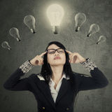 Pretty female manager thinking under lamps Stock Images
