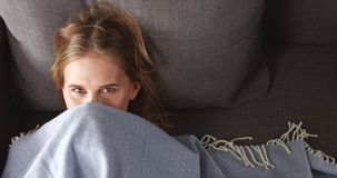 Young blond woman relaxing on the couch. Pretty female model playing peekaboo with a light blue thin blanket lying on a dark grey couch stock video footage