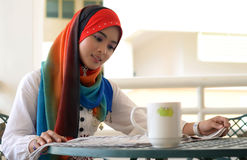 Pretty female Muslim reads newspaper royalty free stock image