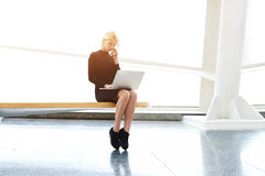 Pretty female with net-book on knees having cell telephone conversation Stock Photo