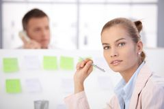 Pretty female office worker sitting at desk Royalty Free Stock Image