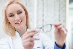 Pretty female ophthalmologist is showing new glasses Royalty Free Stock Photography