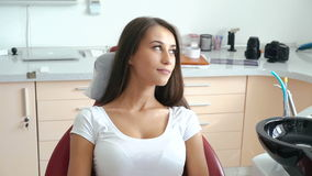 Pretty female patient sitting in dental chair and smiling. Slow motion stock video