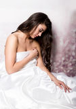 Pretty female in peignoir sleeping on bed under silk sheets Royalty Free Stock Image