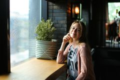 Pretty female person sitting at cafe and smiling. royalty free stock image