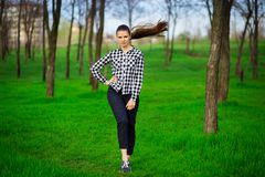 Pretty female person resting in park on green grass. Concept of beauty and leisure time royalty free stock photo