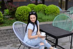 Pretty female person sitting in chair at cafe near green plants and drinking coffee. Concept of leisure time and resting Royalty Free Stock Photo