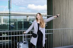 Pretty female person stopping taxi with raised hand, valise and smartpone near airport. stock photography