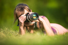 Pretty female photographer lying in grass Stock Image