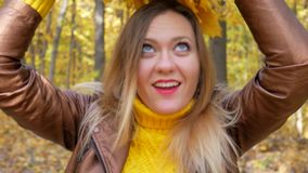 Pretty Woman Put on Maple Leaf Wreath and Smiles. Pretty female put on maple leaf wreath and smiles in forest or park on background of trees with yellow foliage stock video footage