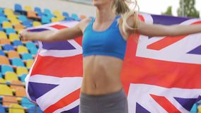 Pretty female runner winning competition, athlete holding flag of Great Britain. Stock footage stock footage