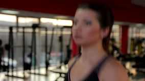 Pretty female running on treadmill at fitness club, successful woman working out stock video