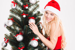 Pretty female in santa claus hat looking at Christmas tree. Pretty joyful young female in red santa claus hat looking at Christmas tree over white background Stock Images