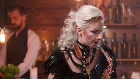 Pretty female saxophonist with bright make up performs in a restaurant stock footage