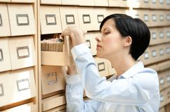Pretty female searches something in card catalog Royalty Free Stock Photos