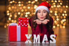 Pretty female sending kiss and lying over glittering background Royalty Free Stock Photo