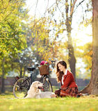 Pretty female sitting down with her dog in a park Stock Photos