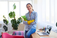 Pretty female sitting on table and holding mop Royalty Free Stock Image